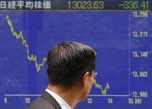 <p>Un uomo davanti al tabellone elettronico che mostra la quotazione del Nikkei. REUTERS/Toru Hanai</p>