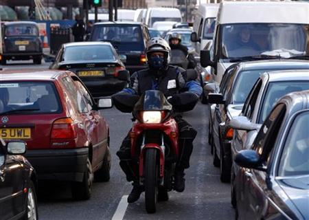 A motorcyclist makes his way through a traffic jam in central London in this file photo. Mayor Boris Johnson has scrapped plans to increase the central London congestion charge to 25 pounds a day for owners of gas-guzzling cars. REUTERS/Stephen Hird