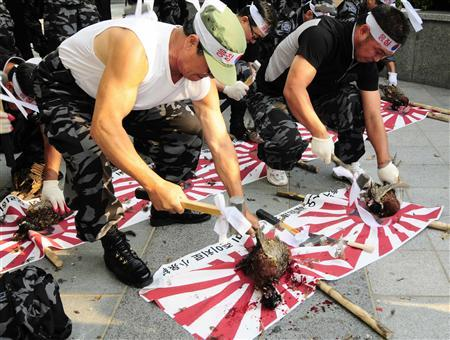Former South Korean spy soldiers who were trained to infiltrate into North Korea beat pheasants to death over portraits of Japanese Prime Minister Yasuo Fukuda (R) and former Japanese Prime Minister Junichiro Koizumi (C) at a rally against Japan's sovereignty claim over a group of desolate volcanic islets Seoul and Pyongyang call Dokdo and Tokyo calls Takeshima, in front of the Japanese embassy in Seoul July 17, 2008. REUTERS/Ben Weller