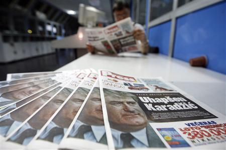 A worker checks the new issue of the day's newspaper, featuring Radovan Karadzic on the front page, in Belgrade July 22, 2008. REUTERS/Marko Djurica