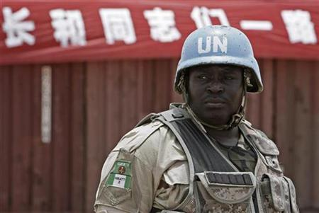 A Nigerian Soldier Serving With The United Nations African Union Mission In Darfur UNAMID Stands Front Of Banner At Parade Following Arrival
