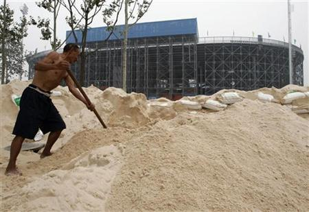 A labourer shovels sand which was transported from south China's Hainan island, in front of the venue for the 2008 Olympics beach volleyball competition at Chaoyang park in Beijing July 26, 2007. The tropical island off China's southern coast provided the 17,000 tonnes of sand shipped to Beijing for the Olympics, and if the athletes' first reactions are anything to go by, it is quickly winning new fans. REUTERS/Alfred Cheng Jin