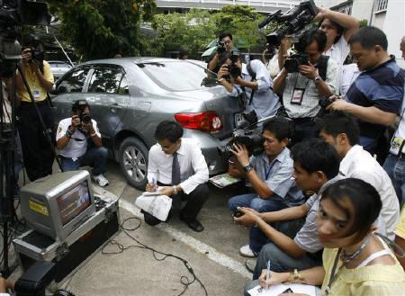 Thai photographers take photos and footage of ousted former Thai Prime Minister Thaksin Shinawatra (seen on television) at the Supreme Court in Bangkok August 11, 2008. REUTERS/Chaiwat Subprasom