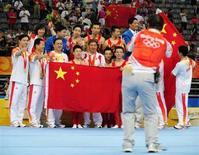 <p>Члены сборной команды КНР по спортивной гимнастике празднуют победу на Олимпиаде в Пекине 12 августа 2008 года. Мужская сборная Китая по спортивной гимнастике выиграла золотые медали в командном первенстве. (REUTERS/Dylan Martinez)</p>