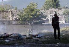 <p>Житель города Гори у разрушенного дома 11 августа 2008 года. Российские самолеты нанесли бомбовый удар по городу Гори в 60 километрах от Тбилиси, ранив нескольких мирных жителей, сообщил корреспондент Рейтер с места событий. (REUTERS/Gleb Garanich)</p>