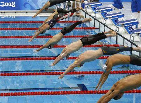 8月13日、北京五輪の競泳で新記録が続出する理由として水着やプール設計など諸説が挙がっている。写真は14日、男子200メートル平泳ぎ決勝で(2008年 ロイター/David Gray)