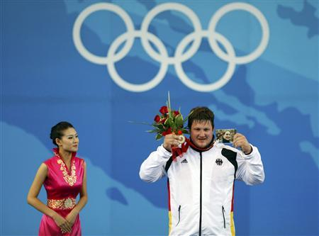 Matthias Steiner of Germany holds a photo of his late wife Susann as he poses with his gold medal in the men's +105kg Group A weightlifting competition at the Beijing 2008 Olympic Games August 19, 2008. REUTERS/Yves Herman