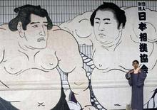 <p>Японка фотографируется у плаката с изображением борцов сумо в Токио. Японская ассоциация сумо в четверг исключила из своих рядов российского борца, арестованного по подозрению в употреблении марихуаны. REUTERS/Kim Kyung-Hoon</p>