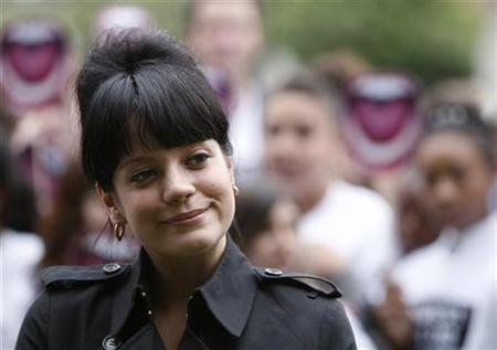 Singer Lily Allen poses for photographs with school children in Parliament Square in London, July 11, 2007. REUTERS/Stephen Hird