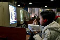 <p>A Chinese girl looks at a computer screen while having her lunch at an internet cafe in Shanghai February 15, 2006. REUTERS/Aly Song</p>