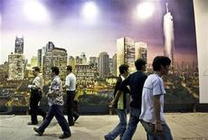 <p>People walk past a poster advertising a new residential compound in downtown Shanghai October 20, 2008. REUTERS/Nir Elias</p>