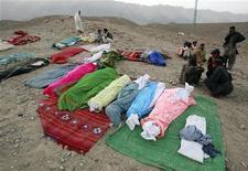<p>Люди ждут, когда будут погребены тела их родных, погибших во время землетрясения в районе Зиарат 29 октября 2008 года. Около 175 человек погибли и почти 1.500 домов были разрушены в результате мощного землетрясения, произошедшего в среду в провинции Белуджистан на юго-западе Пакистана, сообщили представители пакистанских властей. REUTERS/Athar Hussain</p>