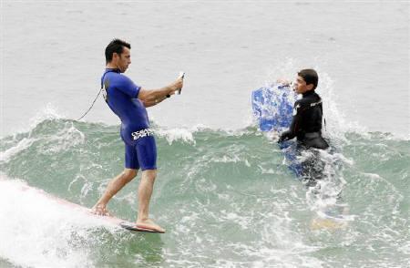 10月31日、シドニーでサーファー用「防水聖書」が登場。写真は防水聖書を読みながら波乗りするサーファー(左)(2008年 ロイター/Daniel Munoz)