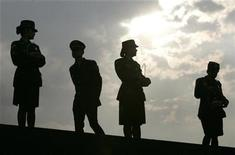 <p>Police officers are seen silhouetted during a military ceremony in Bogota February 27, 2008. REUTERS/Carlos Duran</p>