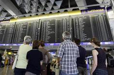 <p>Passengers stand in front of the main information board in the departure hall of Frankfurt airport August 7, 2008. REUTERS/Alex Grimm</p>