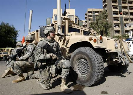 U.S. soldiers take position beside their armoured vehicle after a bomb attack in central Baghdad November 26, 2008. REUTERS/Thaier al-Sudani