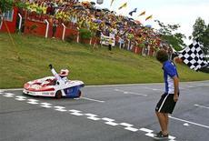 <p>O piloto brasileiro Rubens Barrichello comemora com a torcida vitória no desafio internacional de kart, realizado em Florianópolis e que teve o ex-tenista Gustavo Kuerten dando a bandeirada. REUTERS/Carsten Horst/divulgação.</p>