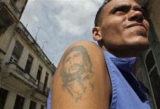 """<p>A man with a tattoo of late rebel leader Ernesto """"Che"""" Guevara poses on a street in Havana December 27, 2008. REUTERS/Stringer</p>"""