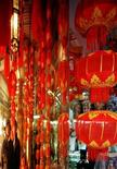 <p>A couple of Japanese tourists are reflected on a glossy pillar as they admire paper lanterns at an art shop in the port city of Tianjin in a file photo. REUTERS/Handout</p>