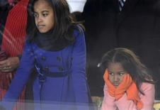 <p>U..S President Barack Obama's daughters Malia (L) and Sasha Obama watch the inaugural parade from their father's reviewing stand in Washington January 20, 2009. Barack Obama became the first black U.S. president on Tuesday and declared it is time to set aside petty differences and embark on a new era of responsibility to repair the country and its image abroad. REUTERS/Jonathan Ernst</p>