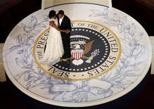 <p>First lady Michelle Obama and President Barack Obama dance on a replica of the presidential seal at the Commander-in-Chiefs Inaugural ball in Washington January 20, 2009. Obama took power as the first black U.S. president on Tuesday and quickly turned the page on the Bush years, urging Americans to rally to end the worst economic crisis in generations and repair the U.S. image abroad. REUTERS/Jim Young (UNITED STATES)</p>