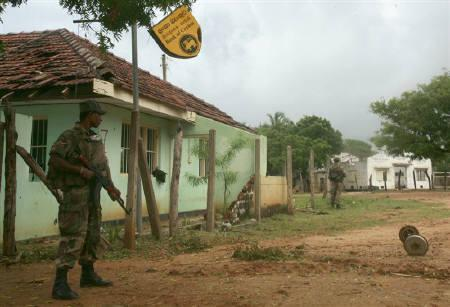 Sri Lankan soldiers stand guard outside a bullet-riddled building that had once housed the Bank of Ceylon in the formerly Tamil Tiger rebel-controlled town of Mullaitvu in north-eastern Sri Lanka January 27, 2009. REUTERS/Bryson Hull