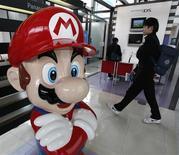"""<p>Un visitante camina cerca de """"Mario"""", un personaje del juego de Nintendo Co Ltd """"Mario Bros"""", en la sala de ventas de la compañías en Tokio, 29 ene 2009. Sony Corp reportó un resultado negativo en su tercer trimestre fiscal y reiteró que espera una pérdida anual récord debido a la caída de la demanda y el alza del yen, mientras que su rival Nintendo Co redujo su pronóstico de todo el año por segunda vez en tres meses. REUTERS/Toru Hanai (JAPON)</p>"""
