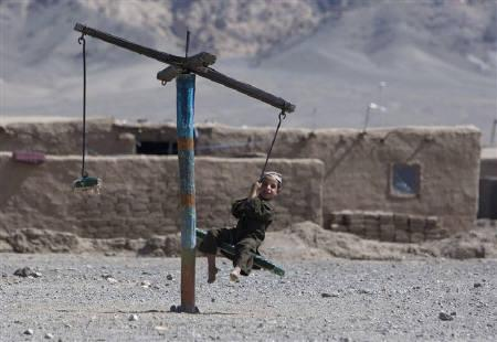 An internally displaced Afghan boy plays on a swing on the outskirts of Herat province, west of Kabul in this picture taken May 28, 2008. REUTERS/Ahmad Masood/Files