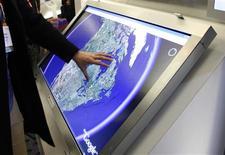 <p>Présentation de Google Earth sur un écran tactile. Le géant de l'internet a lancé une nouvelle version de son logiciel d'exploration virtuelle de l'univers, qui permet désormais de voyager en trois dimensions dans les profondeurs des océans, observer le relief sous-marin et suivre la migration des espèces aquatiques. /Photo d'archives/REUTERS/Rick Wilking</p>