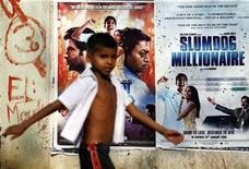 "<p>A boy walks past publicity posters of Golden Globe award-winning film ""Slumdog Millionaire"" in Mumbai January 22, 2009. REUTERS/Arko Datta</p>"