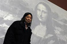 """<p>Chinese-born artist Yan Pei-Ming poses in front of his painting representing """"Mona Lisa"""" during the hanging of his exhibition """"The Funeral of Mona Lisa"""" at the Louvre museum in Paris February 10, 2009. REUTERS/Jacky Naegelen</p>"""