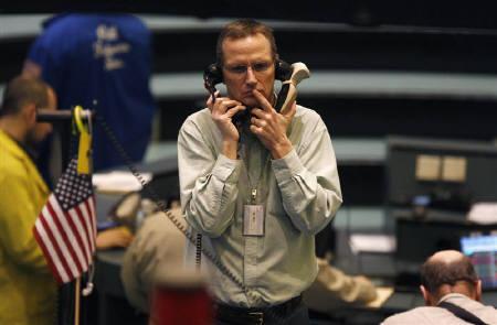 2月20日、ニューヨーク商品取引所の金先物相場は、安全資産買いで一時1000ドルの大台に。写真は12日、ニューヨーク・マーカンタイル取引所の金先物トレーダー(2009年 ロイター/Mike Segar)