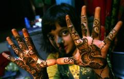 """<p>Rubina Ali, who acted as young Latika in the film """"Slumdog Millionaire"""" shows mehndi painted on her hands in the slum she resides in, prior to leaving for airport to fly to Los Angeles to attend the 81st Academy Awards, in Mumbai February 20, 2009. REUTERS/Arko Datta</p>"""