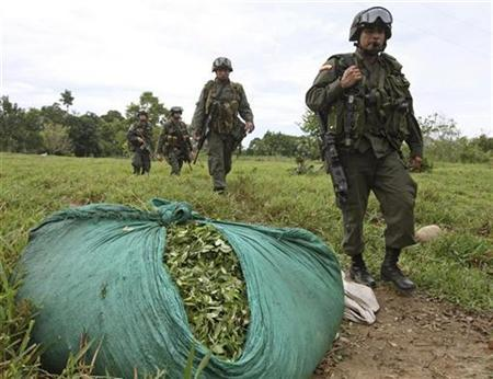 Colombian anti-drug policemen walk past a bag of coca leaves in an area of cocaine laboratories near Saravena, January 20, 2009. REUTERS/Jose Miguel Gomez