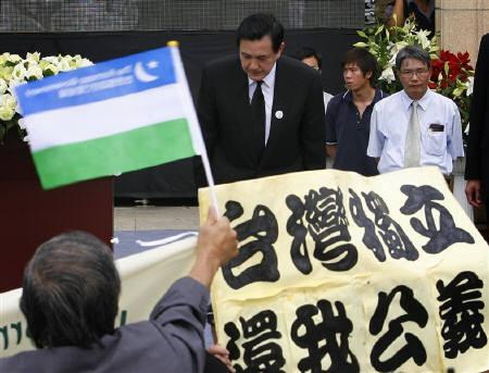 Activists wave banners as Taiwan President Ma Ying-jeou bows during a memorial to commemorate the ''228'' event in Kaohsiung February 28, 2009. REUTERS/Nicky Loh