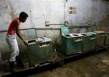 <p>A woman checks a washing machine at a laundromat in Old Havana, as the city prepares for the arrival of heads of state of member countries attending the Non-Aligned Movement summit, September 14, 2006. REUTERS/Jorge Silva</p>