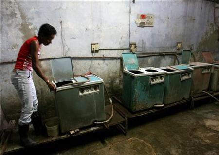 A woman checks a washing machine at a laundromat in Old Havana, as the city prepares for the arrival of heads of state of member countries attending the Non-Aligned Movement summit, September 14, 2006. REUTERS/Jorge Silva