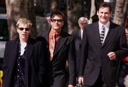 Former members of pop group Spandau Ballet (L-R) John Keeble, Steve Norman and Tony Hadley are seen arriving at the High Court in London in this April 30, 1999 file photo. REUTERS/Ian Waldie/Files