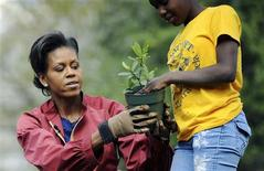 <p>First Lady Michelle Obama (L) helps a student plant herbs in the White House Kitchen Garden on the South Lawn of the White House in Washington April 9, 2009. REUTERS/Jonathan Ernst</p>