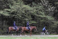 <p>A cyclist rides past policemen on horses searching for a bear who appeared in Tivoli Park, Ljubljana April 16, 2009. REUTERS/Srdjan Zivulovic</p>