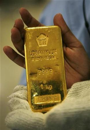 In this file photo an employee holds a one kilogram gold brick at the PT Antam Tbk. precious metal refinery in Jakarta January 15, 2009. REUTERS/Beawiharta