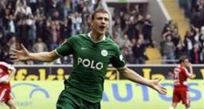 <p>Edin Dzeko comemora após marcar três gols em 12 minutos contra o Hoffenheim neste sábado. A partida terminou em 4 x 0 e ajudou o Wolfsburg a manter a liderança do Campeonato Alemão. REUTERS/Thomas Bohlen</p>