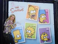 """<p>Nancy Cartwright, the voice of Bart Simpson, signs a poster at the unveiling of the new """"The Simpsons"""" U.S. postage stamps in Los Angeles May 7, 2009. REUTERS/Phil McCarten</p>"""