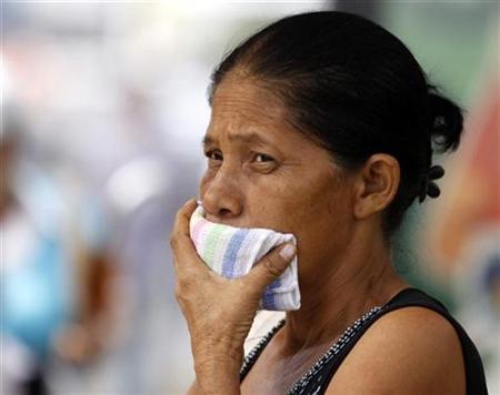 A woman covers her mouth with a towel at a bus stop in Panama City, May 11, 2009. REUTERS/Alberto Lowe