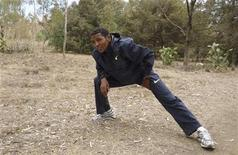 <p>Eritrea's long-distance runner Zersenay Tadesse stretches after his training session in the capital Asmara, May 21, 2009. REUTERS/Andrew Cawthorne</p>