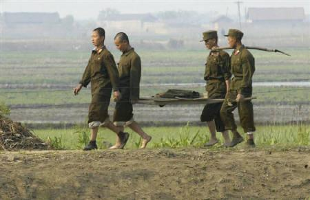 North Korean soldiers walk along the banks of the Yalu River near the North Korean town of Sinuiju, opposite the Chinese border city of Dandong May 27, 2009. REUTERS/Jacky Chen