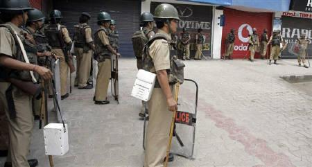 Indian police stand guard in front of closed shops on the fifth day of a strike over the alleged rape and murder of two Muslim women in Srinagar June 5, 2009. REUTERS/Danish Ismail