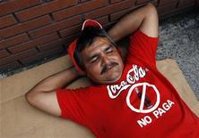 <p>Un ex dipendente di Coca-Cola in Venezuela partecipa a una protesta a Caracas contro la multinazionale, accusata di non pagare la liquidazione. REUTERS/Jorge Silva</p>