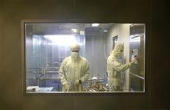 <p>Men in medical suits work inside the AdImmune flu vaccine manufacturing facility in Taichung June 18, 2009. REUTERS/Nicky Loh</p>