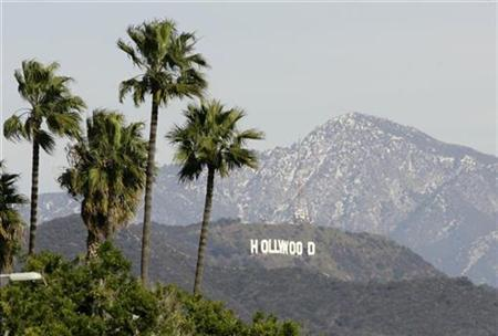 The Hollywood Sign is seen between palm trees and snow dusted mountains in Los Angeles January 7, 2008. REUTERS/Danny Moloshok